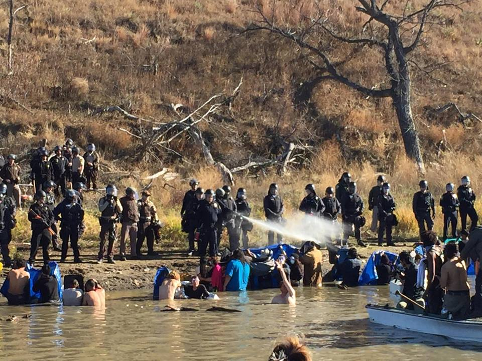 Armed police officers spraying peaceful Standing Rock protesters.