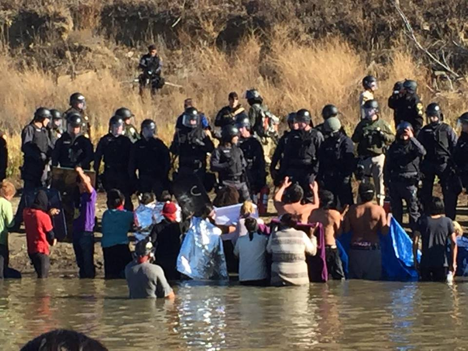 Protesters in Standing Rock, North Dakota, wading toward armed police officers.